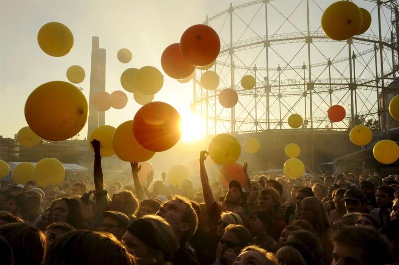 Flow-yleisö nauttii festivaalitunnelmasta auringon laskiessa Helsingin Suvilahdessa.