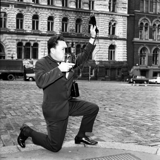Lehtikuvan valokuvaaja Pertti Jenytin poseeraa Helsingin Sanomien mainokseen Erottajalla vuonna 1964.