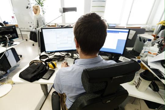 Miestoimittaja työskentelee avokonttorissa kahden tietokonenäytön ääressä.