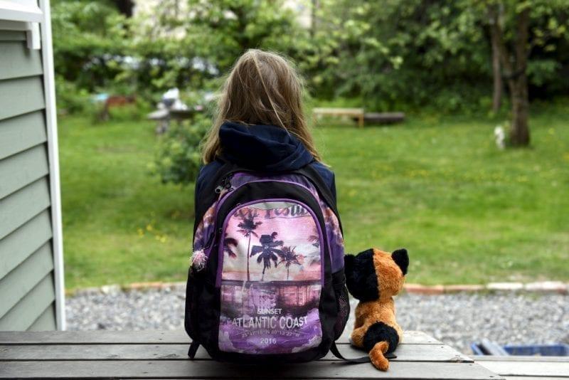 Pieni reppuselkäinen tyttö istuu portailla selin kameraan pehmolelu seuranaan.