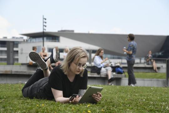 Nuori nainen makailee nurmikolla ja käyttää tablettia.