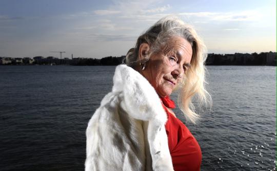 Taiteilija Miina Äkkijyrkkä poseeraa kuvaajalle rannan läheisyydessä.
