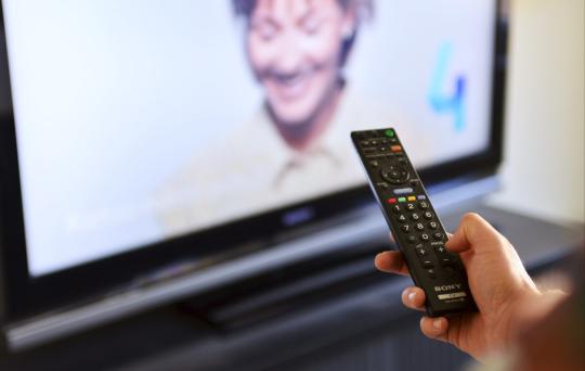 Televisionkatsoja pitelee kaukosäädintä kädessään.