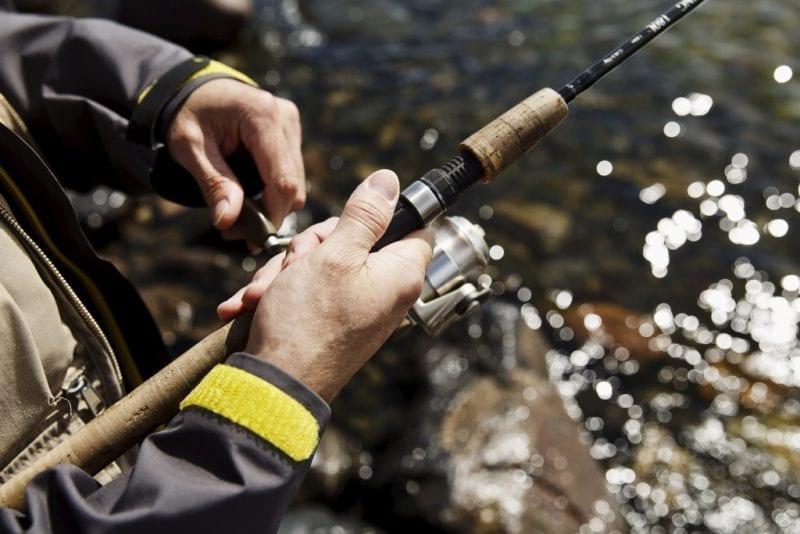 Kalastavan miehen kädet pitelevät virveliä.