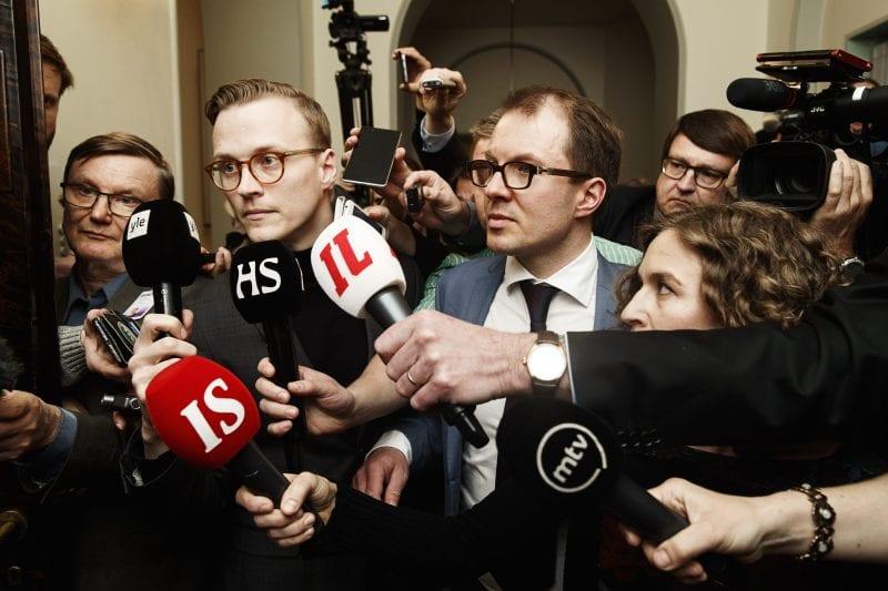 Joukko eri tiedotusvälineiden edustajia mikrofonit esillä eduskunnassa.