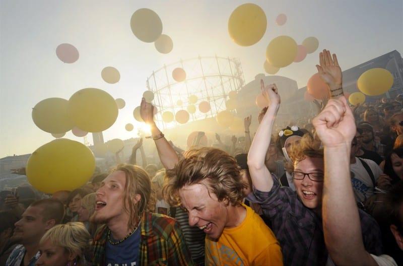 Flow Festivalin yleisö juhlii Helsingin Suvilahdessa auringon laskiessa ja värikkäiden ilmapallojen keskellä.
