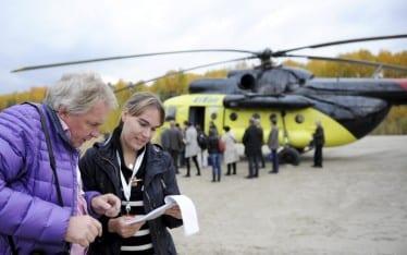 Lehtikuvan Martti Kainulainen ja taloustoimittaja Anniina Luotonen tarkastelevat muistiinpanolehtiön sisältöä, taustalla helikopteri ja muita ihmisiä.