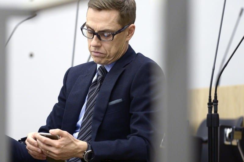 Valtiovarainministeri Alexander Stubb tutkii kännykkäänsä eduskunnan täysistunnossa joulukuussa 2015. Lehtikuva / Heikki Saukkomaa