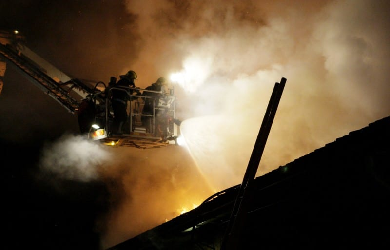 Nostokorin kyydissä olevat palomiehet sammuttamassa palavaa tekniikan museota Helsingissä.