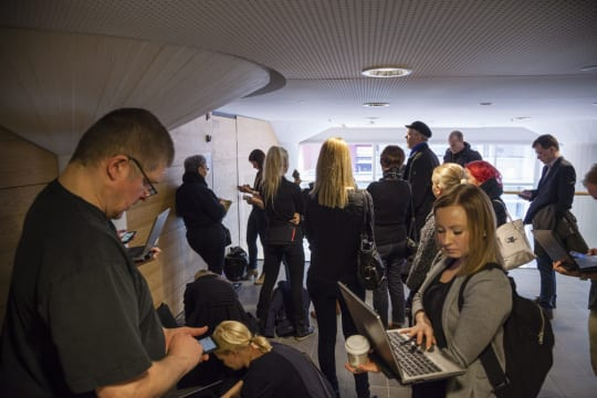 Joukko toimittajia odottamassa Helsingin käräjäoikeuden aulassa.