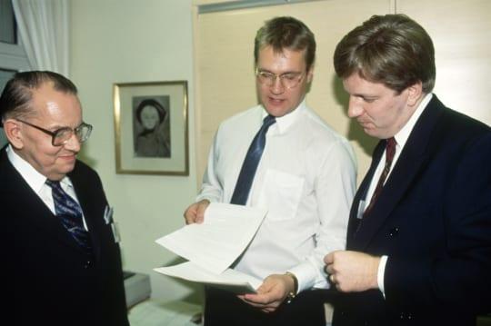 Pääministeri Esko Aho valmistautuu lukemaan STT:n uutisia STT:n studiossa Suomen Tietotoimiston uuden viestintätalon vihkiäisissä 11. marraskuuta 1991. Ohjeita antamassa Kaj Wessman ja Olli-Pekka Behn.