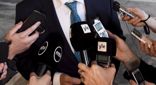 Toimittajat ojentelevat mikrofonejaan saadakseen valtiovarainministeri Petteri Orpon kommentit taltioitua.