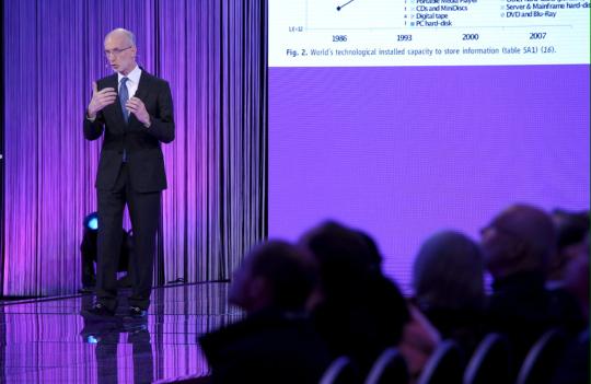 Siististi pukeutunut professori Stuart Parkin luennoi yleisölle violetilla värillä valaistulla lavalla.