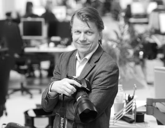 Valokuvaaja Heikki Saukkomaa poseeraa kameran kanssa työpaikallaan Voimatalossa Helsingissä maaliskuussa 2014.