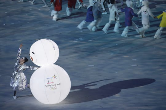 Hopeiseen takkiin pukeutunut tanssija ja lumiukko Sotchin olympialaisten loppunäytöksessä.