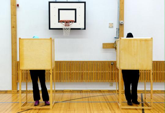Kaksi äänestäjää antaa äänensä vaneriseinäisissä kopeissa koulun liikuntasalissa.