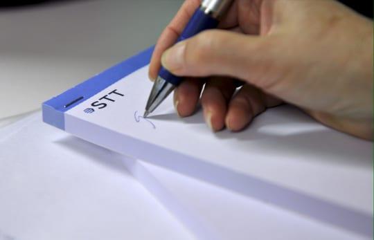 Kynä kädessä kirjoittaa lehtiöön.