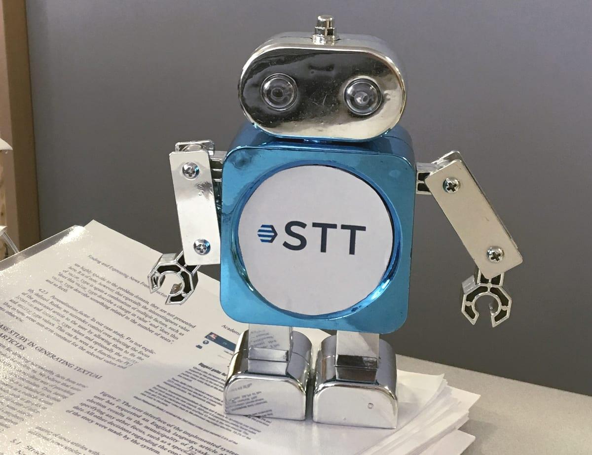 Lelurobotti, jonka rintaan on liimattu STT:n logo, seisoo paperinivaskan päällä.
