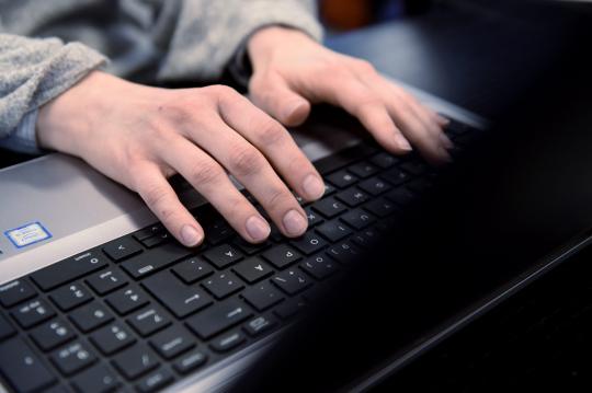 Kommenttien moderaattorin sormet tietokoneen näppäimistöllä.
