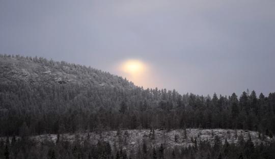 Aurinko pilkistää tunturin takaa.