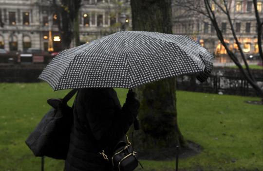 Tummaan takkiin pukeutunut nainen kävelee sateenvarjo kädessään kaupungilla.