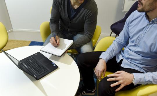 Kaksi miestä, joista toinen tekee muistiinpanoja kalenteriin, istuu keltaisissa tuoleissa toimistossa ja keskustelee keskenään.