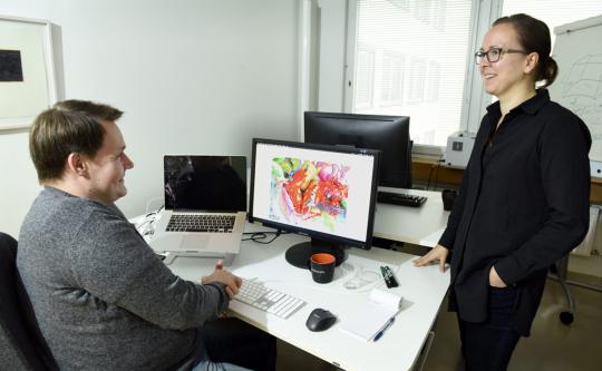 Mies ja nainen keskustelevat hyväntuulisen näköisinä työpöydän äärellä.