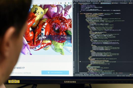 Ohjemistokehittäjä tutkii kuvakaupan lähdekoodia tietokoneen näytöltä.