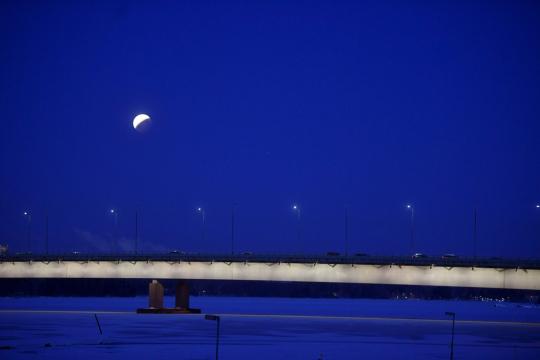 Sininen yötaivas ja kuu Helsingissä Länsiväylän yllä.