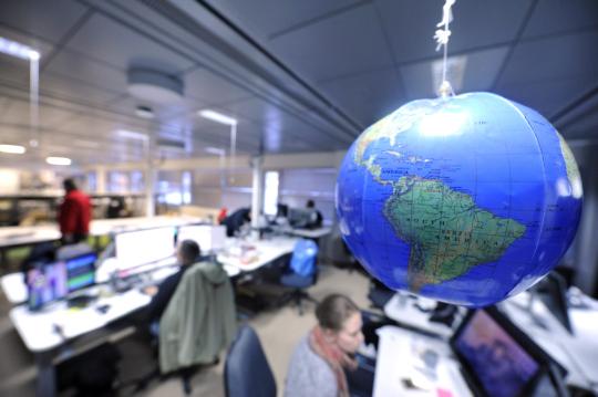 Toimituksen väkeä työpisteillään STT:n tiloissa Ruoholahdessa, etualalla karttapallo.