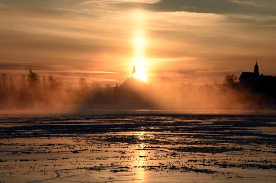 Nouseva aurinko saa jään ja höyryn hehkumaan oranssinkirjavana Helsingin Kauppatorin rannassa.