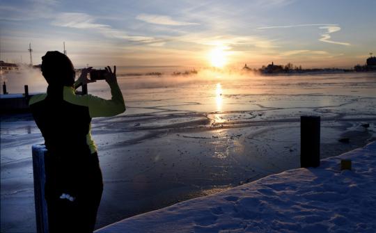 Urheilu-asuun ja pipoon pukeutunut nainen ottaa kuvaa auringonnoususta talvisena aamuna Helsingin Kauppatorin rannassa.