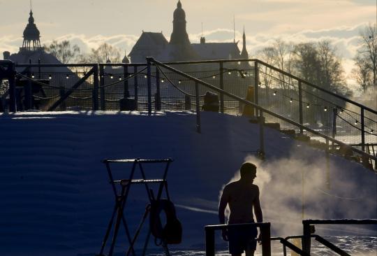 Uimari höyryää talvisena aamuna Allas Sea Pool -merikylpylässä Helsingissä.
