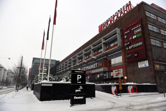 Kauppakeskus Ruoholahden rakennus ja mainoskylttejä kuvattuna lumisena talvipäivänä.