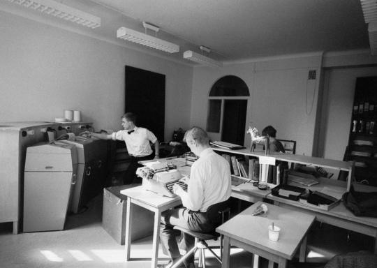 Suomen Tietotoimiston työntekijöitä ja toimituksen laitteistoa Mannerheimintien toimitiloissa, mustavalkoinen valokuva vuodelta 1967.
