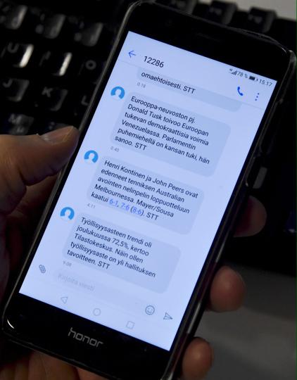 Mies selaa matkapuhelimellaan saamiaan STT:n tekstiviestiuutisia.