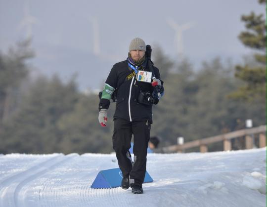 Uutiskuvaaja Vesa Moilanen kävelee ladun viertä kamerakalustoa kantaen.