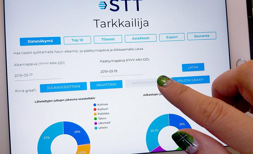 Värikkäästi lakatut sormenkynnet tabletin näytöllä, jolla näkyy STT Tarkkailija -työkalun hakunäkymä.