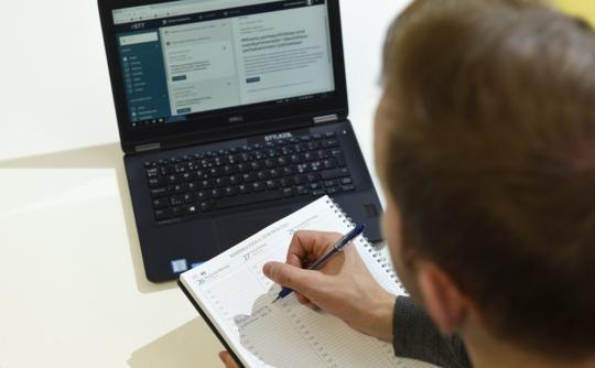 Mies katsoo kannettavalta tietokoneelta STT Pro -palvelun sisältöä ja kirjoittaa merkintää kalenteriinsa.