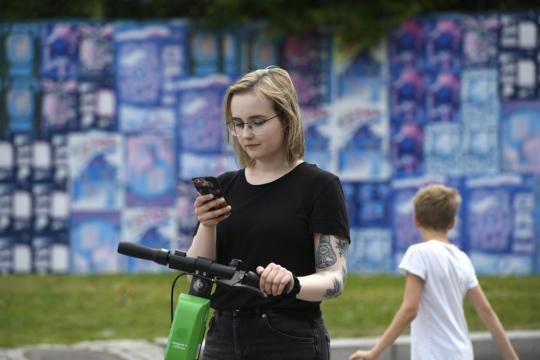 Nuori, tatuoitu nainen on pysähtynyt sähköpotkulaudan kanssa selatakseen älypuhelinta.