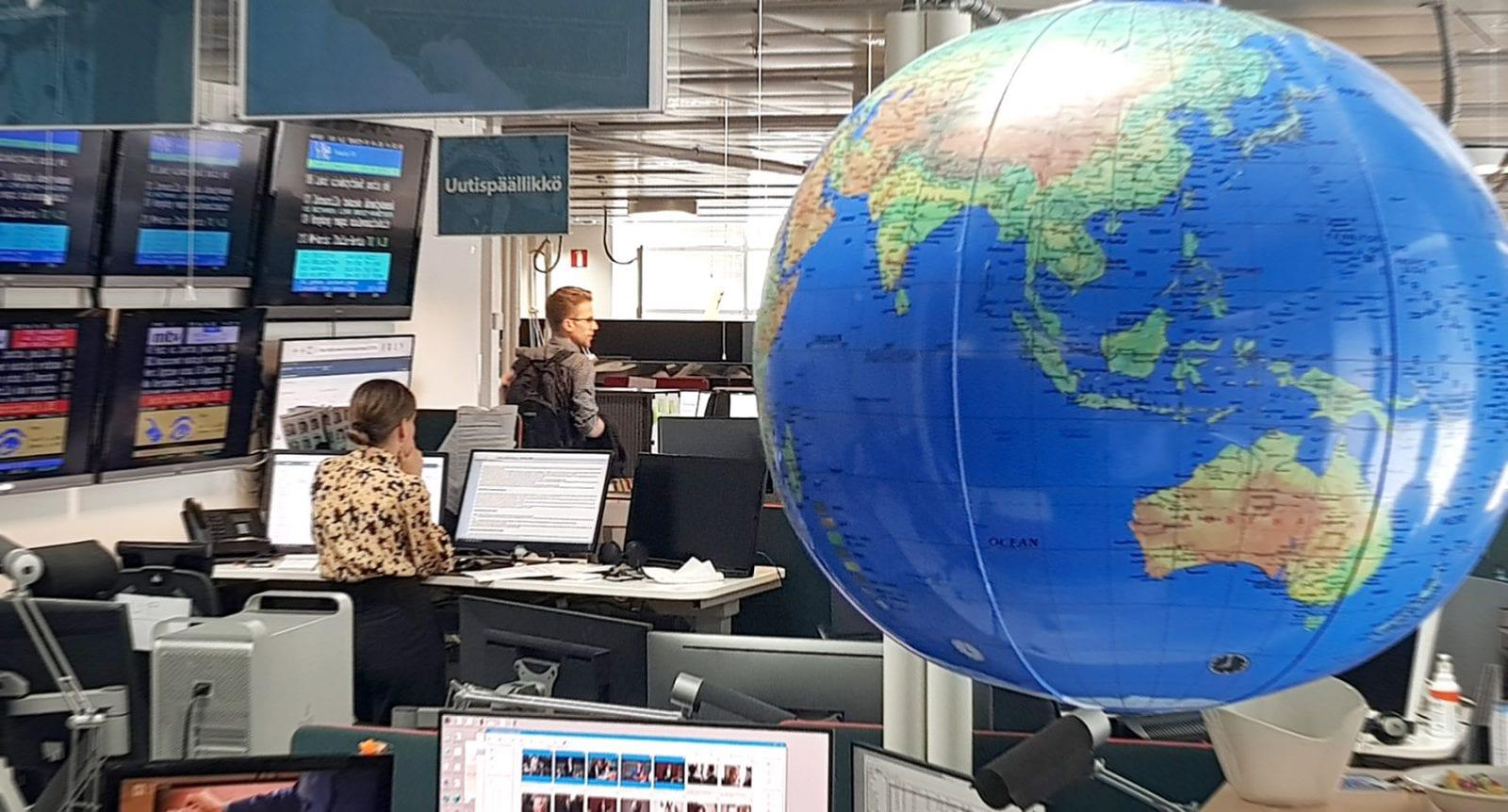 STT:n uutistoimitus Ruoholahdessa, etualalla karttapallo ja Australia.