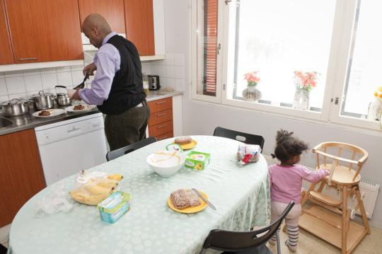 Tummaihoinen isä laittaa ruokaa keittiössä, pieni tytär ottaa tukea syöttötuolista.