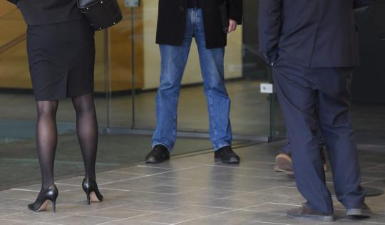 Bisnesasuisen naisen, farkkumiehen ja pukumiehen jalat.