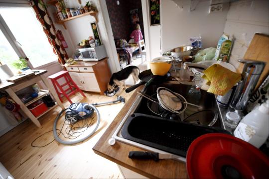 Värikkäästi sisustetun kodin keittiössä on tiskejä altaassa, imuri lattialla ja koira aterioimassa ruokakupillaan,
