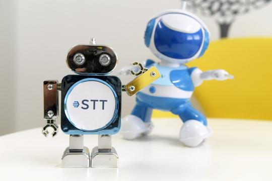 Kaksi lelurobottia, joista toiseen on liimattu STT:n logo, seisoo pöydällä.