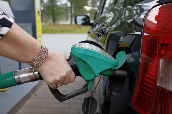 Ismo Pekkarisen kuvituskuva, jossa nainen tankkaa autoa.
