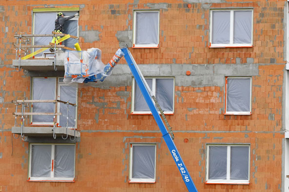 Ismo Pekkarisen kuvituskuva, jossa rakennusmies seisoo ulkona parvekkeella korjaten ikkunaa.