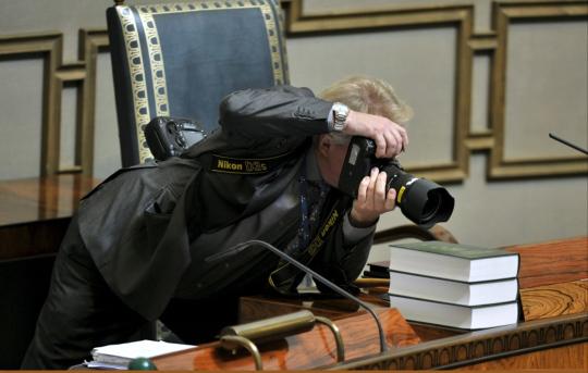 Uutiskuvaaja Martti Kainulainen sihtailee kamerallaan eduskunnassa.