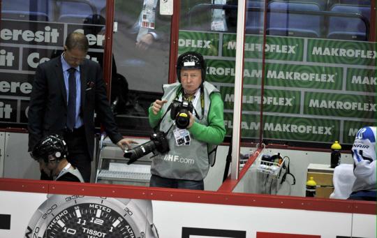 Uutiskuvaaja Martti Kainulainen kypärä päässä jääkiekkokaukalon laidalla.