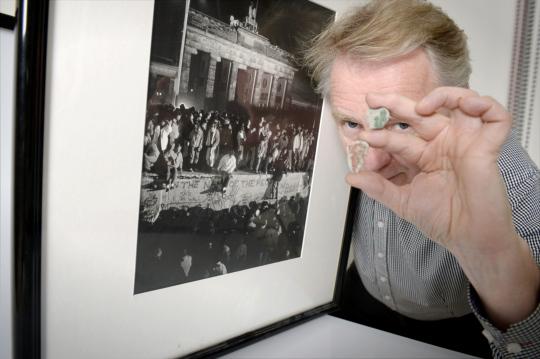 Martti Kainulainen pitelee kehystettyä valokuvaa Berliinin muurin murtumisesta ja kahta muurin palasta.